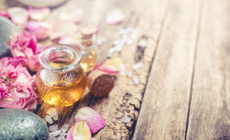 Massage oil, petals flowers and zen stones. SPA background in a rustic style with copyspace. Shallow DOF