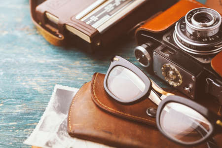 70s: Old retro glasses, radio and Old retro camera from 70s on wooden background. Stock Photo