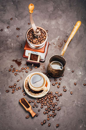 Grinder, cezve,  and a cup of freshly brewed coffee on a dark background Stock Photo