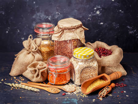 Cereal grains, yellow peas, red lentils, beans on a dark background. Healthy food background