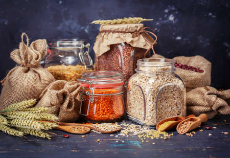 Cereal grains, oatmeal, yellow peas, red lentils, beans on a dark background 写真素材