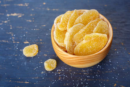 spicy cooking: Candied ginger in a wooden bowl. Food background Stock Photo