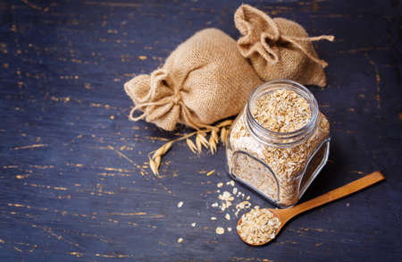 oats: Oatmeal in a glass jar on a dark background - healthy food