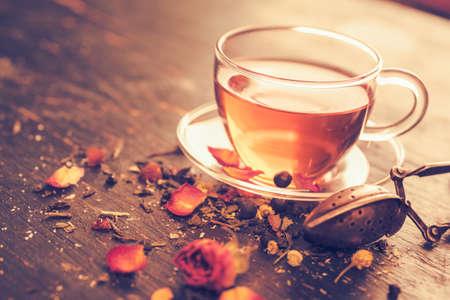 Vers gebrouwen thee, glazen thee kopje met droge rozebudden. Droge thee en thee kopje op een oude houten tafel. Vintage getinte