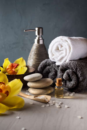 spa flower: SPA still life. Orchid flower, towel, aroma oils and zen stones, Stock Photo