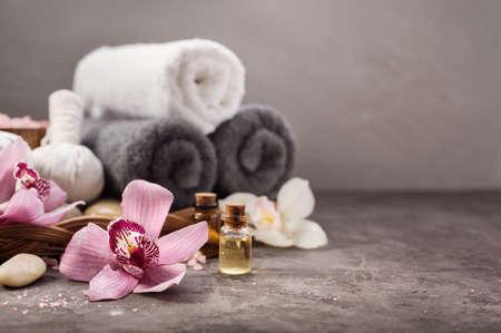 Fondo del balneario con la flor de la orquídea y el aceite de masaje en la mesa. Fondo de Spa con copyspace