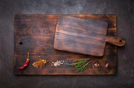Épice pour cuisiner et des planches à découper vides sur un fond sombre. Fond de nourriture avec copyspace. Vue de dessus