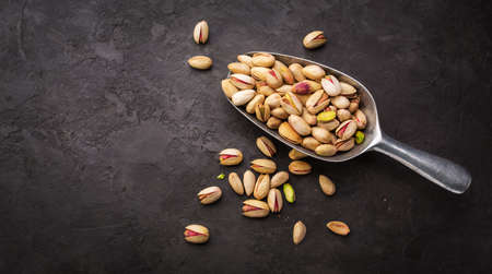 pistachios: Pistachios in a scoop on a dark background. Food background with copyspace Stock Photo
