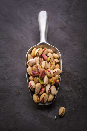 pistachios: Pistachios in a scoop closeup. Pistachios over dark background