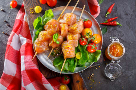 shishkabab: Raw chicken on wood skewers with tomatoes and lettuce. Top view