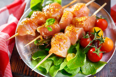 shishkabab: Raw chicken on wood skewers with tomatoes and lettuce. Shallow DOF