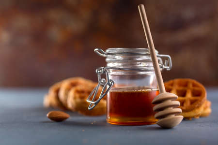 stirrer: delicious honey in a jar close up. Food background concept