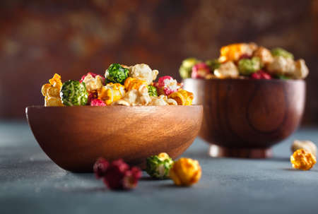 Colored popcorn. Fruit flavored popcorn in wooden bowl. Shallow DOF
