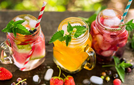 Refreshing drinks with ice in jars, orange juice, berry juice and watermelon water 免版税图像