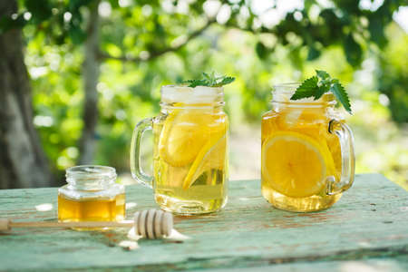 field mint: Iced tea with lemon slices and mint. A refreshing drink on a hot summer day in the garden. Shallow depth of field Stock Photo