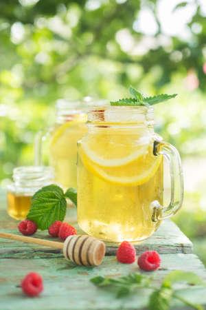 té helado: El té helado con rodajas de limón y frambuesa. Una bebida refrescante en un día caluroso de verano en el jardín. Poca profundidad de campo Foto de archivo