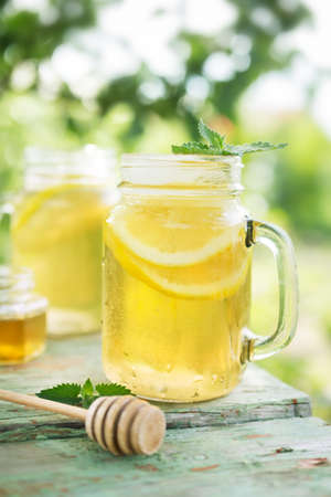 minty: Iced tea with lemon slices and mint. A refreshing drink on a hot summer day in the garden. Shallow depth of field Stock Photo
