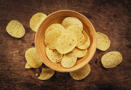 potatoes: Crispy potato chips in bowl on wooden background. Closeup. Food background, top view