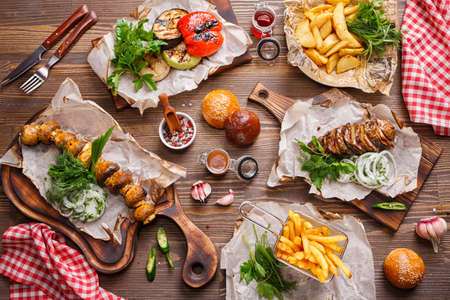 Different food on a wooden table. Grilled vegetables, baked potatoes, French fries and Grilled mushrooms. Food background, Top view