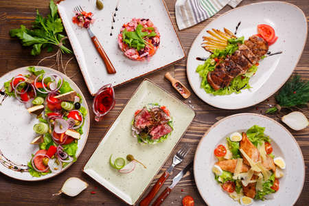 chicken caesar salad: Different salads on wooden table, top view. Vegetable salad, Salad with smoked duck, Grilled chicken Caesar salad.