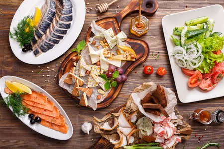 smoked: Various delicacies on the table. Cheese platter, sliced smoked salmon, mackerel, bacon, and vegetable salad. Food background, Top view