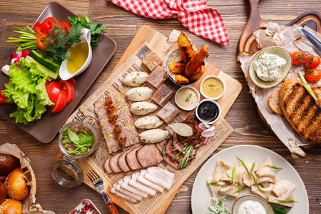smoked: Delicious meat antipasti, vegetables salad and croutons on a wooden background, top view. Food concept
