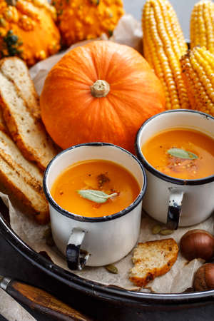 Pumpkin cream soup with spices in a white vintage mugs. Autumn background Stock Photo