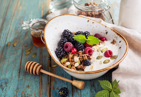 Delicious breakfast with fresh berries and honey on a old wooden table. Healthy breakfast. Selective focus