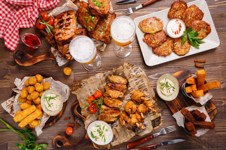 cultures: Grill Dinner table. BBQ Pork and ribs, Grilled chicken wings and legs served with souce and two glasses of beer. Stock Photo