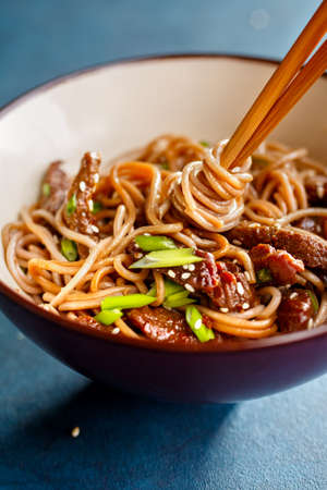 Asian soba noodles with beef and sesame, close-up.