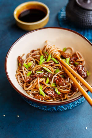 Fried noodles yakisoba with beef and sesame seeds in a bowl with chopsticks. Asian cuisine meal.