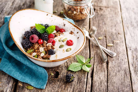berry: Homemade granola with blackberry and milk. Healthy breakfast ingredients. Rustic style.