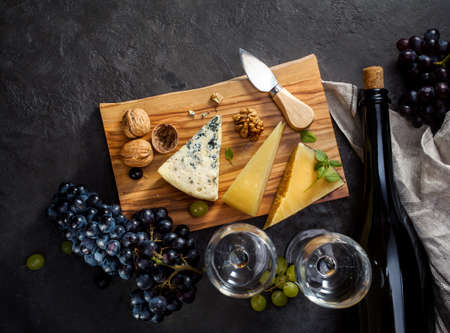 delicatessen: Blue cheese, parmesan, wine and grapes on dark stone background.