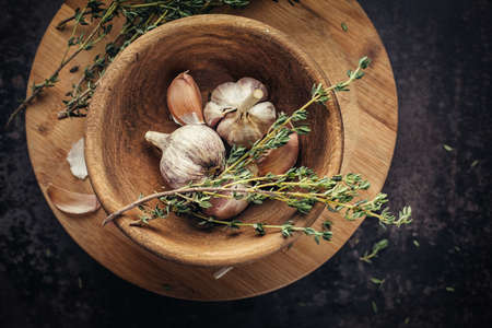 utensils: Garlic and thyme in a wooden bowl on a dark table from above. Stock Photo