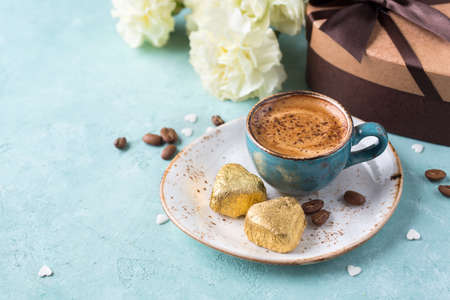 Coffee mug with yellow and chocolates on blue rustic table from above. Valentines Day background or Womens day