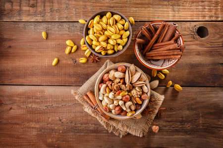 allergic ingredients: Mix of nuts and cinnamon on a old rustic table. Stock Photo