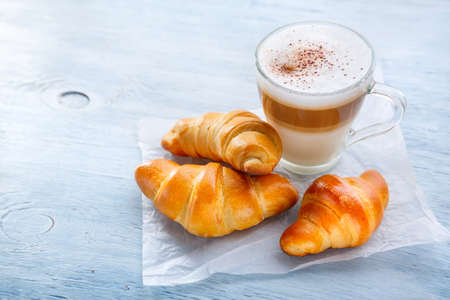 Breakfast with Latte macchiato coffee and croissants. Selective focus Stock Photo