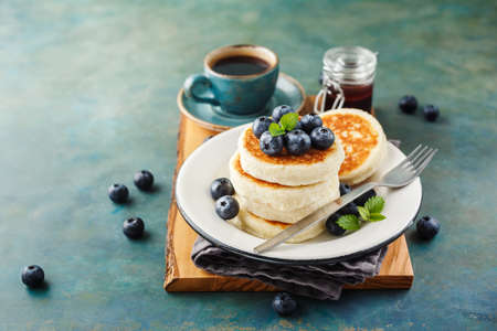Cottage cheese pancakes with blueberries and coffee, Healthy Breakfast. Stock Photo