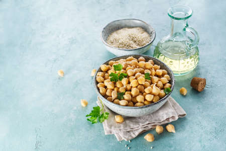 Ingredients for cooking hummus. Chickpeas, sesame seeds and oil. Food background with copy space for your text. Stock Photo - 78348820
