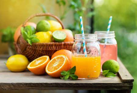 Mix of fresh citrus fruits in basket and juice in glass jars. Grapefruit and orange juice Stock Photo