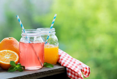 Grapefruit and orange juice in glass jars in the open air. Food background with copy space for your text. Selective focus. Imagens