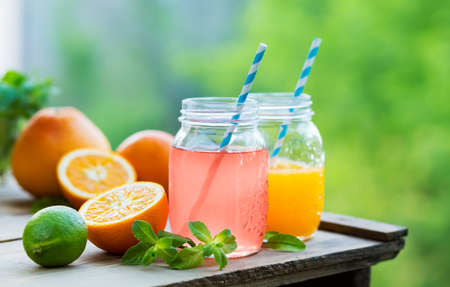 Grapefruit and orange juice in glass jars in the open air. Concept for healthy eating and nutrition. Selective focus.