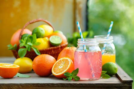 Grapefruit and orange juice in glass jars in the open air. Fresh Detox Juices. Concept for healthy eating and nutrition. Selective focus.
