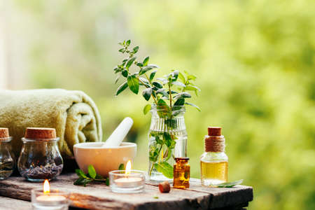 Spa background with essential oil, fresh peppermint and towel on wooden table outdoors. Selective focus. Stock Photo