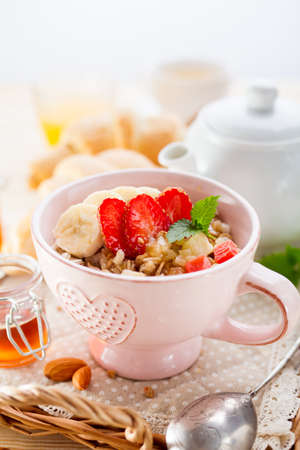 Oatmeal with banana and strawberries. Delicious Breakfast. Stock Photo