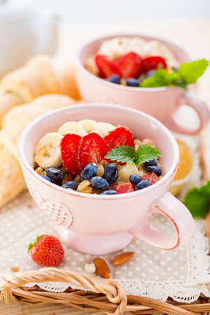 Porridge with banana and fresh berries in a cups. Healthy eating Stock Photo - 80230589