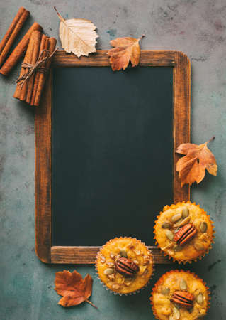 Freshly baked pumpkin muffins and cinnamon sticks with empty chalkboard.