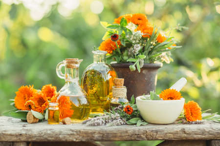 Spa composition with Fresh herbs, calendula and different types of oils. Selective focus.