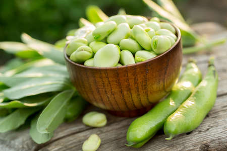Fresh broad beans in a bowl on an outdoor wooden picnic table. Stok Fotoğraf