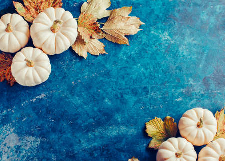 Decorative pumpkins on blue shabby background. Holiday background with copyspace.